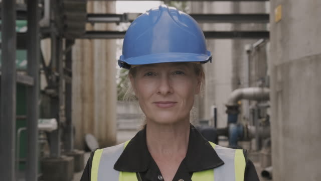 portrait of female industrial worker looking at camera wearing high vis vest and hard hat helmet - manufacturing occupation stock videos & royalty-free footage