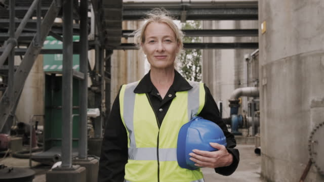 portrait of female industrial worker looking at camera wearing high vis vest and holding hard hat helmet - hat stock videos & royalty-free footage