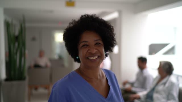vidéos et rushes de verticale de l'infirmière mûre femelle à l'hôpital - origine ethnique