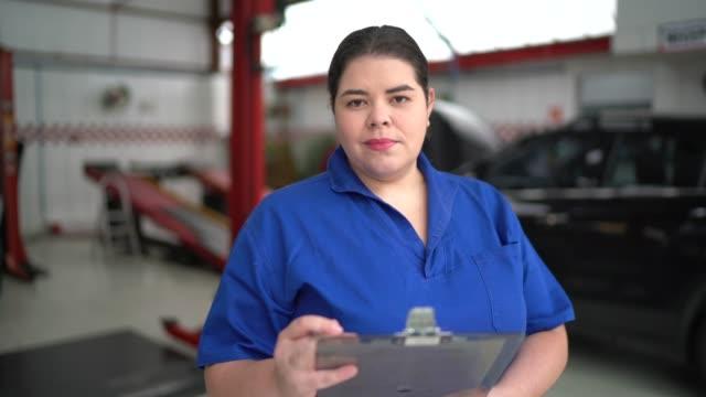 Portret van vrouwelijke werktuigkundige die in autoautoreparatie werkt