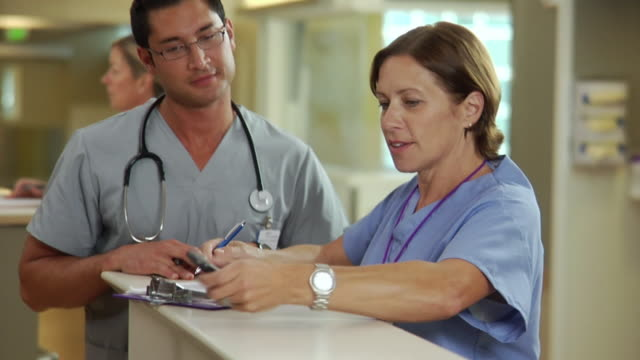 cu portrait of female nurse and doctor filling out patient's charts in hospital, seattle, washington, usa - maschio con gruppo di femmine video stock e b–roll