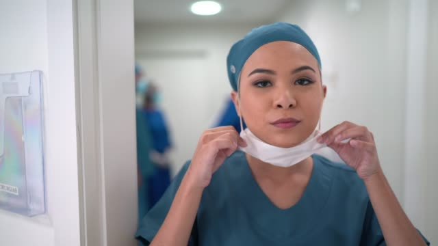 portrait of female nurse dressing up face mask at hospital - applying stock videos & royalty-free footage