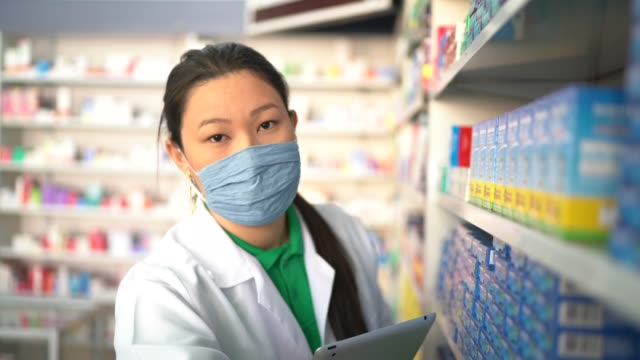 vídeos de stock e filmes b-roll de portrait of female pharmacist picking some drugs with face mask at pharmacy - serviços essenciais