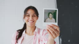 Portrait Of Female Photographer On Photo Shoot Holding Up Instant Polaroid Print In StudioÊ