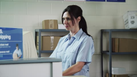 ms pan portrait of female postal worker behind post office counter / orem, utah, usa - post structure stock videos & royalty-free footage