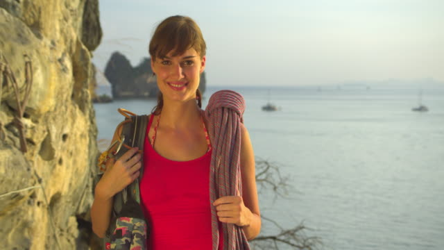 vidéos et rushes de cu portrait of female rockclimber smiling with climbing equipments standing by rock facerock face, ocean and pinnacles in background / krabi, thailand - rock face