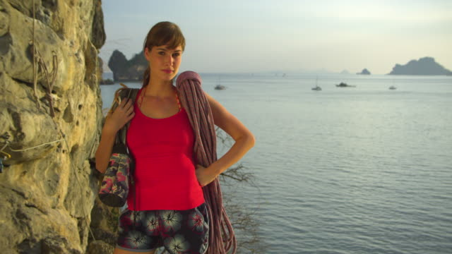 vidéos et rushes de ms portrait of female rockclimber with climbing equipments standing by rock facerock face, ocean and pinnacles in background / krabi, thailand - rock face