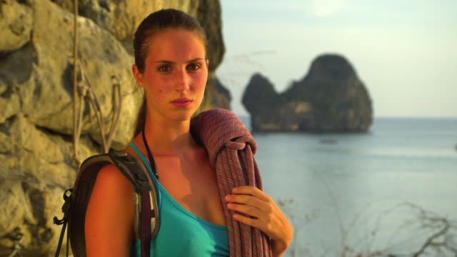 cu portrait of female rockclimber with climbing equipments standing by rock facerock face, ocean and pinnacles in background / krabi, thailand - rock face stock videos & royalty-free footage