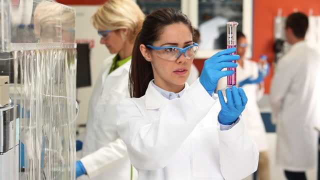 portrait of female scientist in lab - centro di ricerca video stock e b–roll