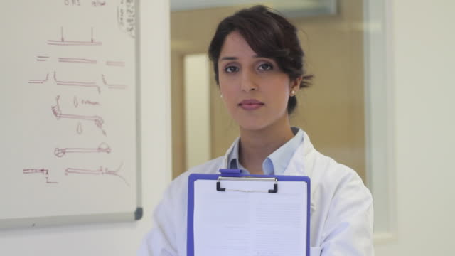 vidéos et rushes de portrait of female scientist in laboratory - bloc note