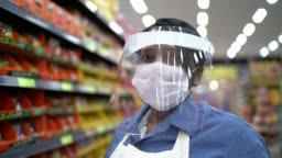 Portrait of female senior supermarket employee or owner with face shield using digital tablet