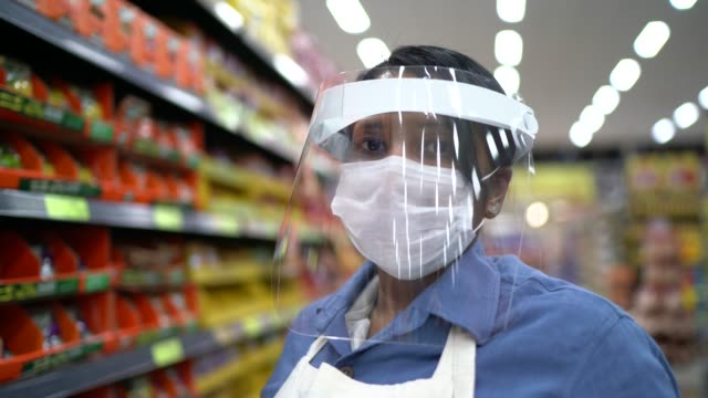 portrait of female senior supermarket employee or owner with face shield using digital tablet - responsibility stock videos & royalty-free footage