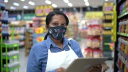 Portrait of female senior supermarket employee or owner with face mask using digital tablet