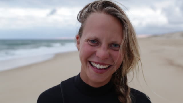 stockvideo's en b-roll-footage met portrait of female surfer at the beach looking into camera, laughing, smiling. - frankrijk
