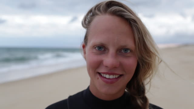 Portrait of female surfer at the beach looking into camera, laughing, smiling.
