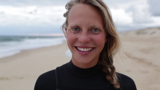 portrait of female surfer at the beach looking into camera, laughing, smiling. - offenes lächeln stock-videos und b-roll-filmmaterial