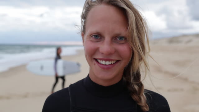 vidéos et rushes de portrait of female surfer at the beach looking into camera, laughing, smiling. - sourire à pleines dents