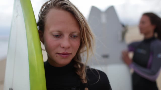 Portrait of female surfer with surfboard at the beach in France.