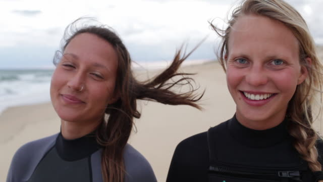 vidéos et rushes de portrait of female surfers at the beach looking into camera, laughing, smiling. - queue de cheval