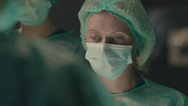 portrait of female surgeon performing surgical operation - surgeon stock videos & royalty-free footage