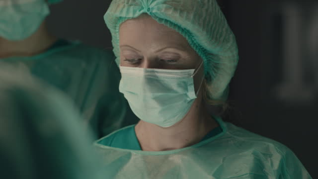 portrait of female surgeon performing surgical operation - guanto indumento protettivo video stock e b–roll