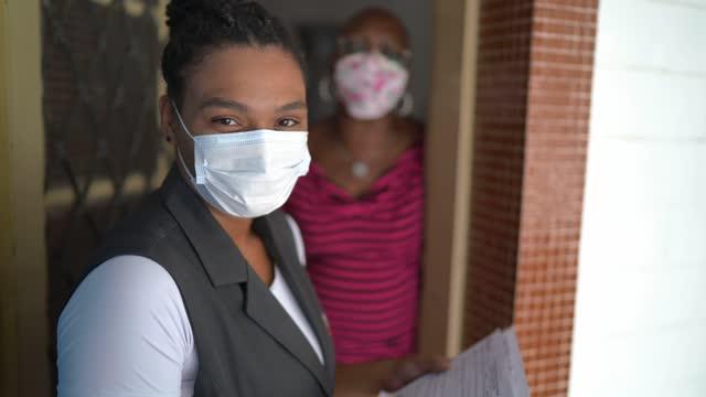 シニア女性の家の玄関先にある女性測量士の肖像画 - フェイスマスクを着用 - 国勢調査点の映像素材/bロール