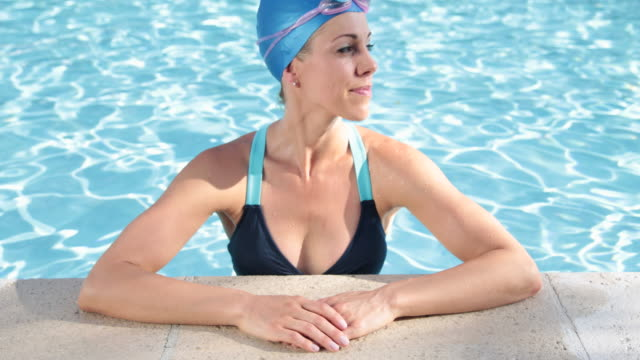 portrait of female swimmer at pool edge putting on goggles and swimming away - swimming cap stock videos and b-roll footage