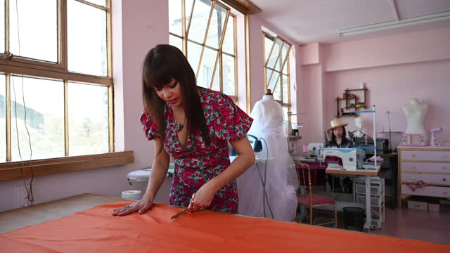 portrait of female tailor cutting fabric in pink atelier - workbench stock videos & royalty-free footage