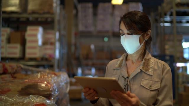 vídeos y material grabado en eventos de stock de retrato de una trabajadora de almacén con máscara facial usando una tableta digital - lista de chequeo