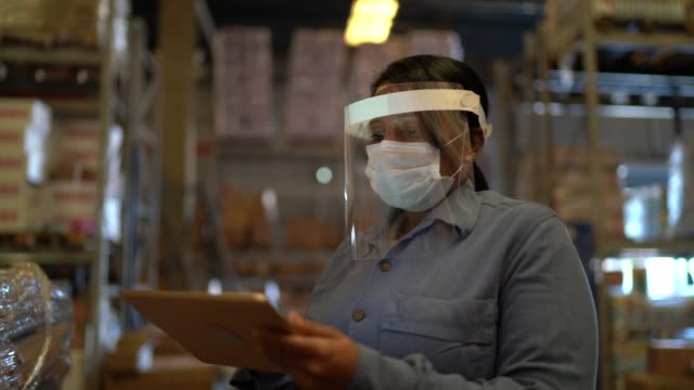 portrait of female warehouse worker with face shield using digital tablet - distribution warehouse stock videos & royalty-free footage