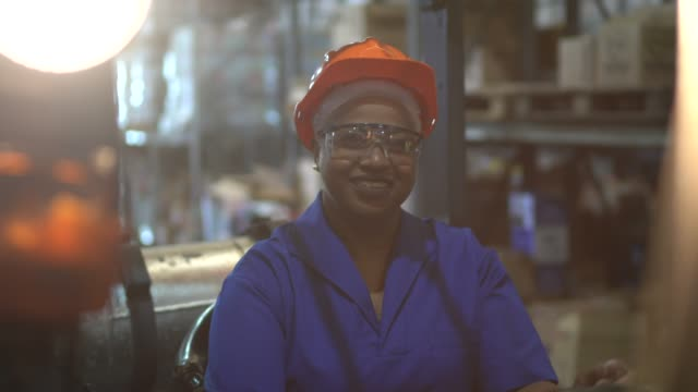 portrait of female worker driving forklift in warehouse - box container stock videos & royalty-free footage