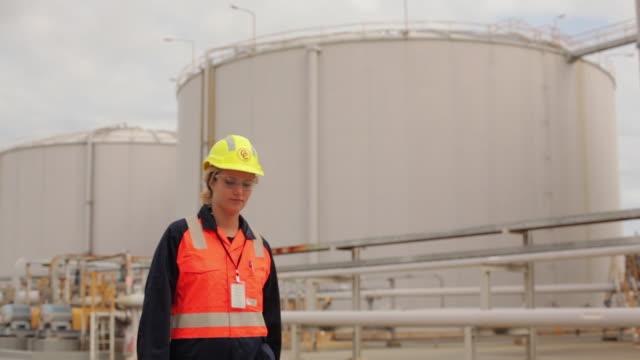 ms portrait of female worker in front of refinery storage tank / perth, australia - 発電所関係の職業点の映像素材/bロール
