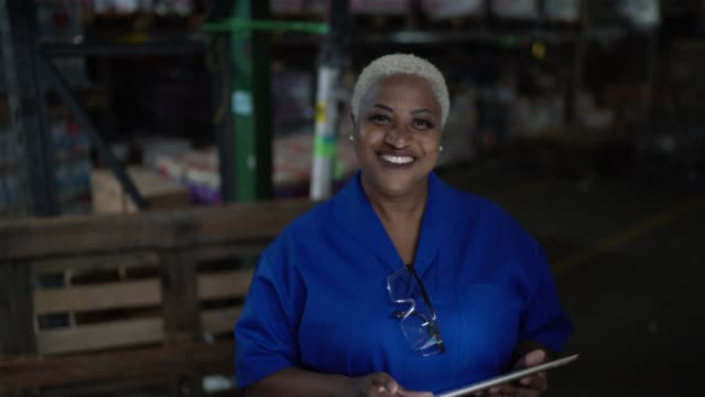 portrait of female worker using digital tablet in warehouse - body positive stock videos & royalty-free footage