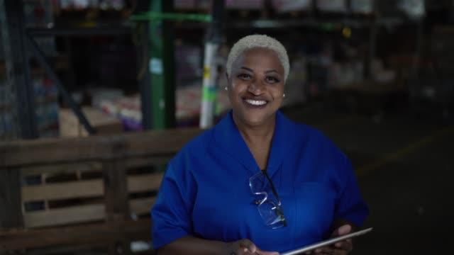 porträt einer arbeiterin mit digitalem tablet im lager - body positivity stock-videos und b-roll-filmmaterial
