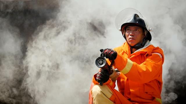 porträt von feuerwehrmann man im feuer an wand von rauch - retter rettungsaktion stock-videos und b-roll-filmmaterial