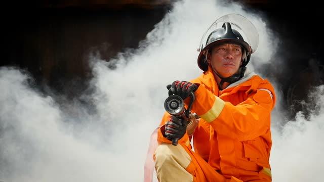 vídeos y material grabado en eventos de stock de retrato de hombre de bombero en incendio operación en pared de humo - manguera