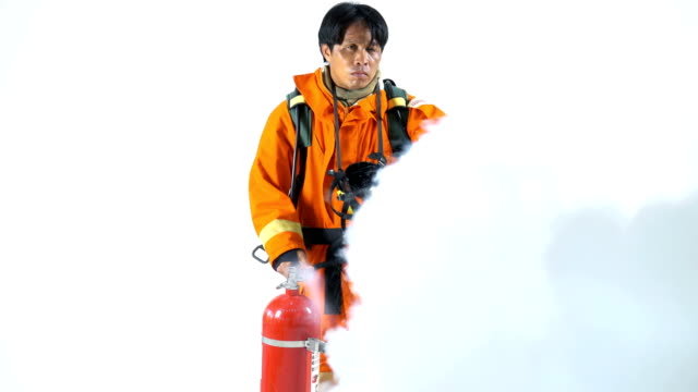 4k portrait of firefighter using fire extinguisher against on white studio background - fire station stock videos & royalty-free footage