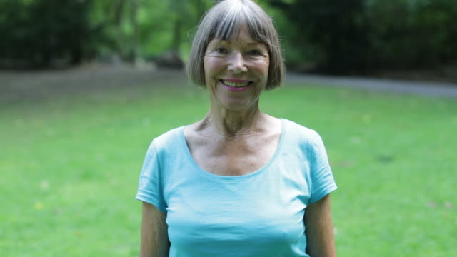portrait of fit senior woman smiling at park - bangs stock videos & royalty-free footage