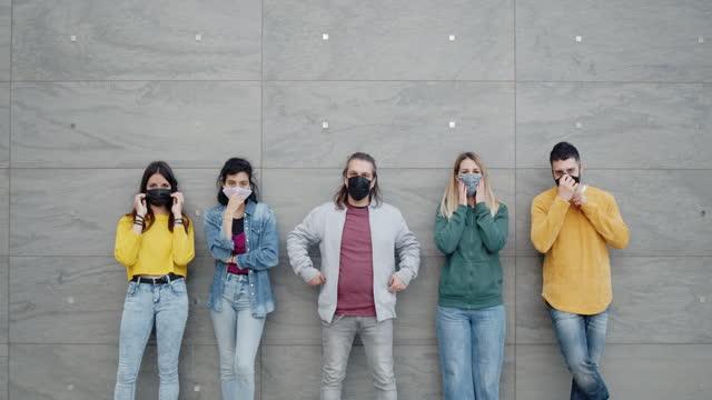 porträt von fünf freunden, die ihre schützenden gesichtsmasken ausziehen und lächeln - herunterlassen stock-videos und b-roll-filmmaterial