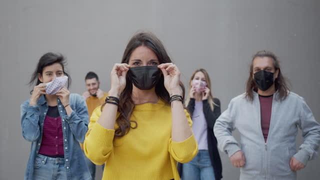 porträt von fünf freunden, die schützende gesichtsmasken tragen und in die kamera schauen - herunterlassen stock-videos und b-roll-filmmaterial
