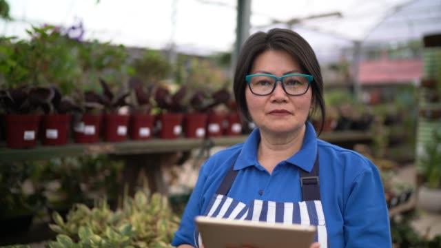 porträt des floristen mit tablet im small business flower shop - in den fünfzigern stock-videos und b-roll-filmmaterial