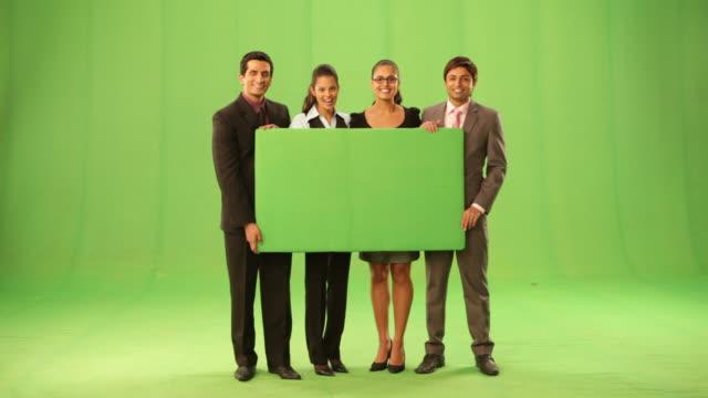 vídeos de stock, filmes e b-roll de portrait of four business people showing a placard  - fundo verde
