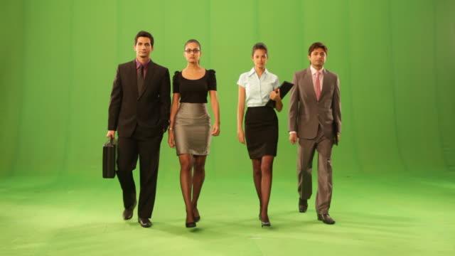 Portrait of four business people walking