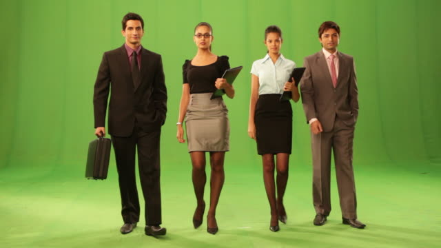 stockvideo's en b-roll-footage met portrait of four business people walking  - groene acthergrond
