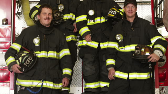 MS TU Portrait of four firefighters posing by fire engine in garage, Pleasant Grove, Utah, USA
