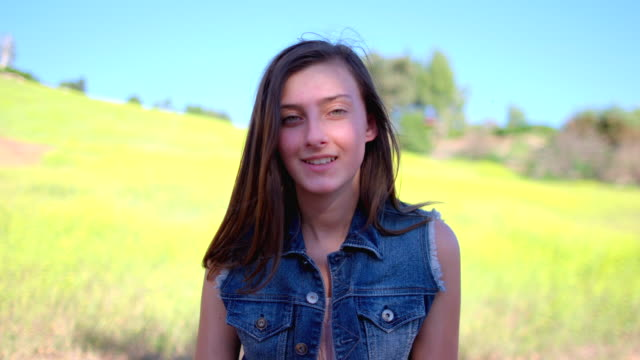 ms slo mo portrait of fourteen year old girl sitting in beautiful mustard field with smiling pensively / thousand oaks, california, united states - mustard stock videos and b-roll footage