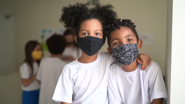 portrait of friends embracing wearing face mask at school - brazil stock videos & royalty-free footage