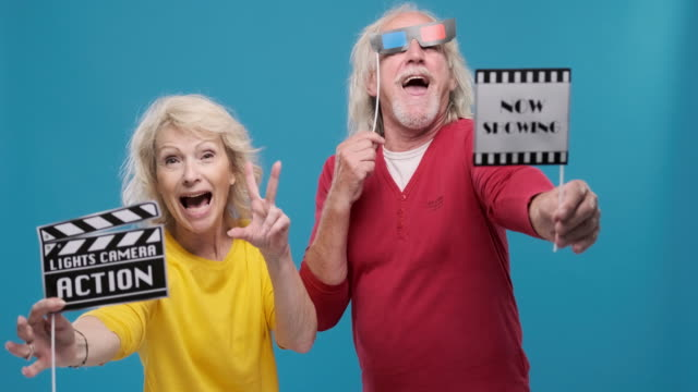 portrait of fun senior couple holding movie props - film slate stock videos & royalty-free footage