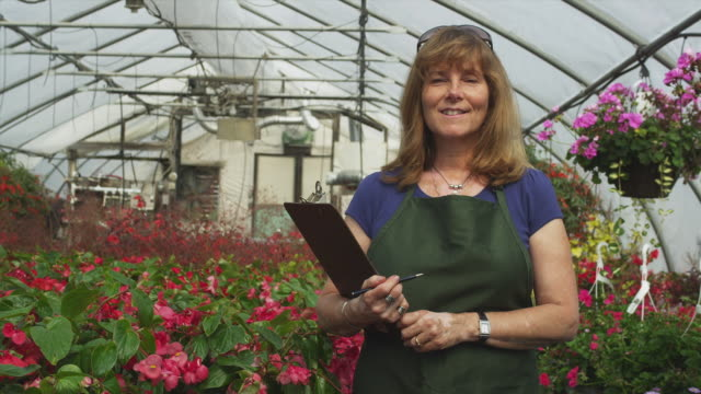 vidéos et rushes de ms portrait of garden center employee standing with clipboard in greenhouse , manchester, vermont, usa - manchester vermont