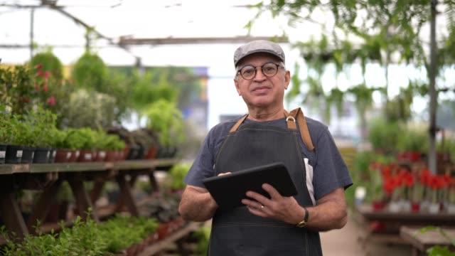 vídeos de stock, filmes e b-roll de retrato de jardim mercado funcionário / proprietário usando tablet digital - feirante
